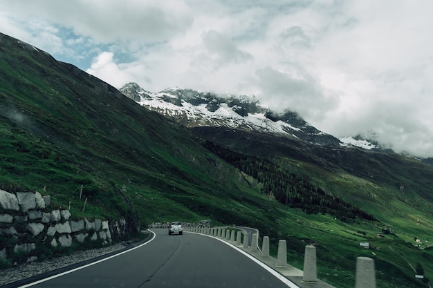 Road in swiss alps mountains in summer cloudy weather