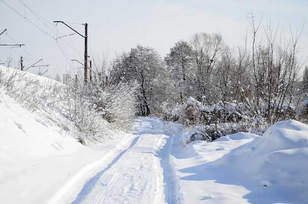 The road that lies parallel to the railway line is covered with snow
