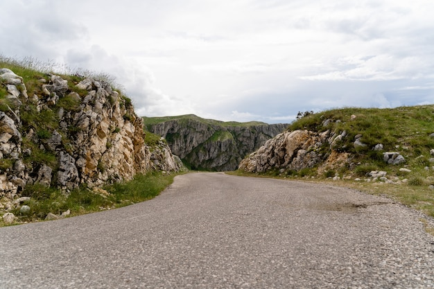 Road through geological formations and rocky mountains under the cloudy sky