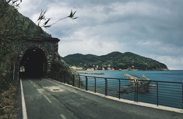 Road towards a tunnel in the mountain near a sea with mountains