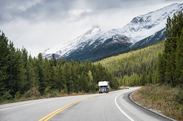 Road trip of camper van driving on highway with rocky mountains in pine forest at banff national park