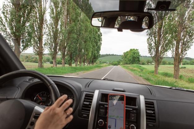 도로 여행 개념 여성이 전화로 스티어링 휠 탐색에 손을 얹습니다.