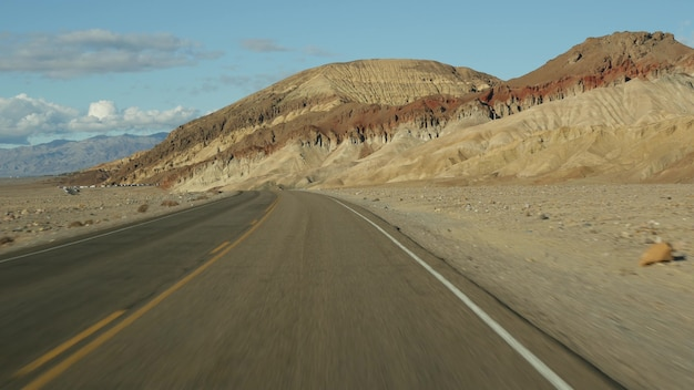 Road trip to death valley artists palette drive california usa hitchhiking auto traveling in america highway colorful bare mountains and arid climate wilderness view from car journey to nevada