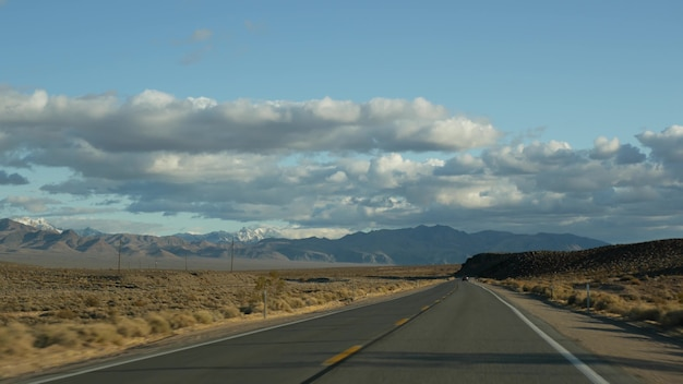 Road trip, driving auto from death valley to las vegas, nevada usa. hitchhiking traveling in america. highway journey, dramatic atmosphere, clouds, mountain and mojave desert wilderness. view from car