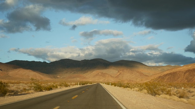 Road trip, driving auto from death valley to las vegas, nevada usa. hitchhiking traveling in america. highway journey, dramatic atmosphere, sunset mountain and mojave desert wilderness. view from car.