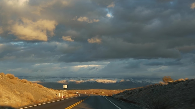 Road trip, driving auto from death valley to las vegas, nevada usa. hitchhiking traveling in america. highway journey, dramatic atmosphere, sunset mountain and mojave desert wilderness. view from car