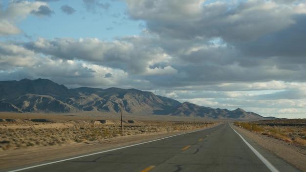 デスバレーから米国ネバダ州ラスベガスまで自動車を運転するロードトリップ。アメリカを旅するヒッチハイク。高速道路の旅、劇的な雰囲気、雲、山、モハーベ砂漠の荒野。車からの眺め