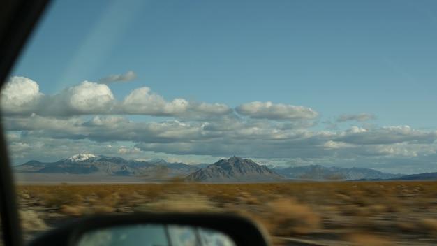 Поездка на автомобиле из долины смерти в лас-вегас, штат невада, сша. путешествие автостопом по америке. путешествие по шоссе, драматическая атмосфера, облака, горы и пустыня мохаве. вид из машины