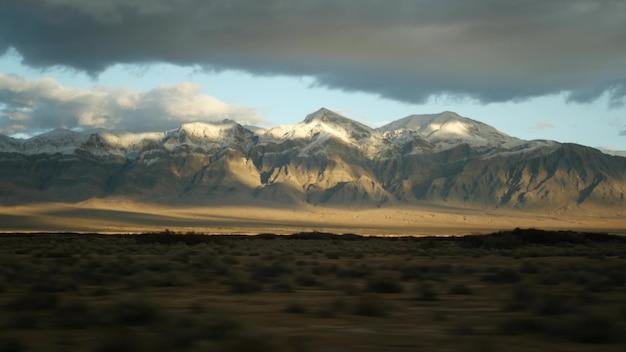 デスバレーから米国ネバダ州ラスベガスまで自動車を運転するロードトリップ。アメリカを旅するヒッチハイク。高速道路の旅、ドラマチックな雰囲気、夕日の山、モハーベ砂漠の荒野。車からの眺め。