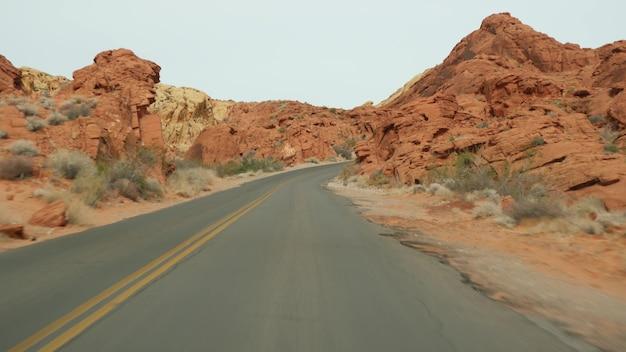 ロードトリップ、米国ネバダ州ラスベガスのバレーオブファイアで自動車を運転。アメリカを旅するヒッチハイク、高速道路の旅。赤いエイリアンの岩層、モハーベ砂漠の荒野は火星のように見えます。車からの眺め。