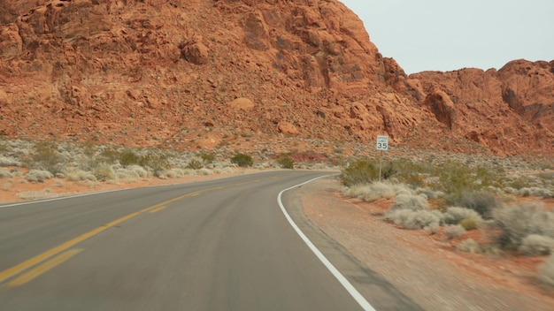 Road trip, driving auto in valley of fire, las vegas, nevada, usa. hitchhiking traveling in america, highway journey. red alien rock formation, mojave desert wilderness looks like mars. view from car.