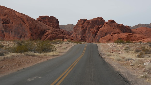 Road trip driving auto in valley of fire las vegas nevada usa hitchhiking traveling in america highway journey red alien rock formation mojave desert wilderness looks like mars view from car