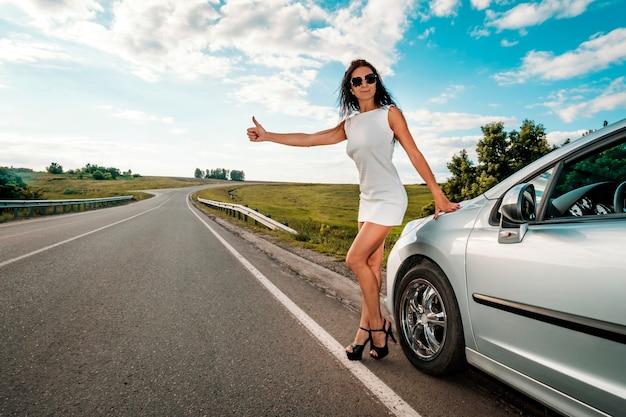 ロードトリップ、ヒッチハイク、旅行、ジェスチャー、人々のコンセプト-田舎道で親指を立てるジェスチャーで車をヒッチハイクして停止する女性