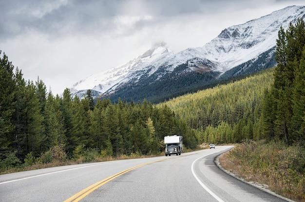 밴프 국립 공원의 소나무 숲에서 록키 산맥이있는 고속도로에서 운전하는 캠퍼 밴의 도로 여행