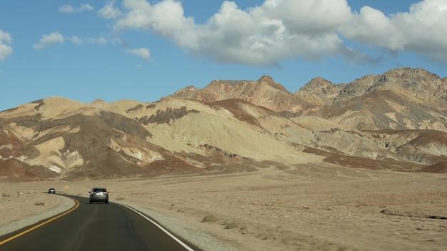 미국 캘리포니아주 아티스트 팔레트 드라이브 데스 밸리로의 로드 트립. 미국에서 히치하이킹 자동차 여행. 고속도로, 다채로운 벌거벗은 산과 건조한 기후의 황야. 차에서 봅니다. 네바다로의 여행.