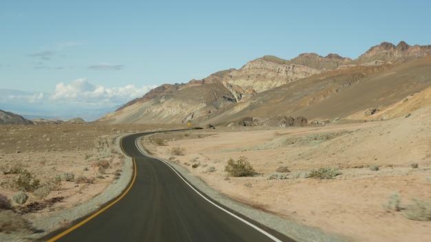 アメリカカリフォルニア州、アーティスツパレットドライブのデスバレーへのロードトリップ。アメリカでのヒッチハイク自動車旅行。高速道路、色とりどりの裸の山々、乾燥した気候の荒野。車からの眺め。ネバダへの旅。