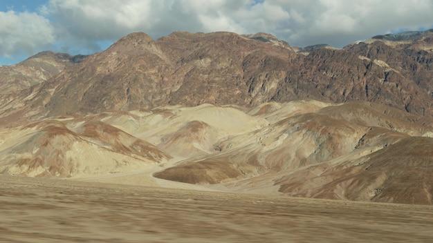 Поездка в долину смерти, привод палитры художников, калифорния, сша. автостоп автопутешествие по америке. шоссе, красочные голые горы и пустыня с засушливым климатом. вид из машины. путешествие в неваду.