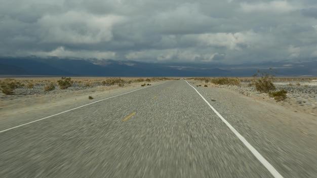 미국 캘리포니아에서 자동차를 운전하는 데스 밸리로의 로드 트립. 미국을 여행하는 히치하이킹. 고속도로, 산과 건조한 사막, 건조한 기후의 황야. 자동차에서 승객 pov입니다. 네바다로의 여행.