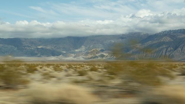 アメリカ、カリフォルニアで自動車を運転するデスバレーへのロードトリップ。アメリカを旅するヒッチハイク。高速道路、山、乾燥した砂漠、乾燥した気候の荒野。車からの乗客のpov。ネバダへの旅。