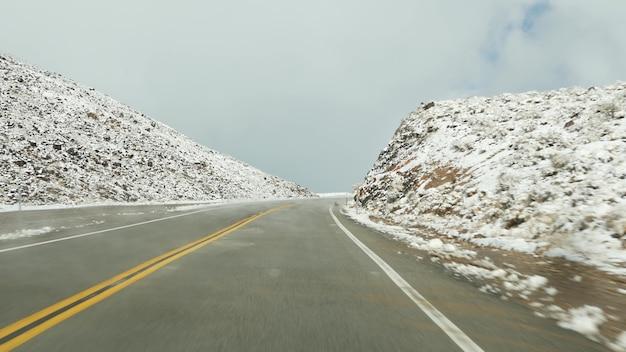 데스 밸리로의 도로 여행, 자동차 운전, 미국 캘리포니아의 눈. 미국으로 여행하는 겨울 히치하이킹. 고속도로, 산길, 메마른 황무지. 자동차에서 승객 pov입니다. 네바다로의 여행.