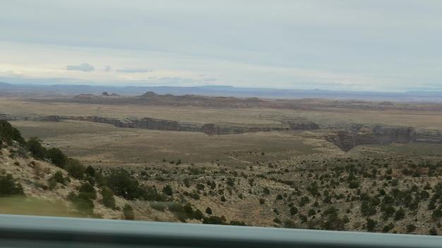Поездка в гранд-каньон, штат аризона, сша, на автомобиле по южному краю. путешествие автостопом по америке, местное путешествие, спокойная атмосфера дикого запада, индийские земли. рельеф плато колорадо через окно автомобиля.