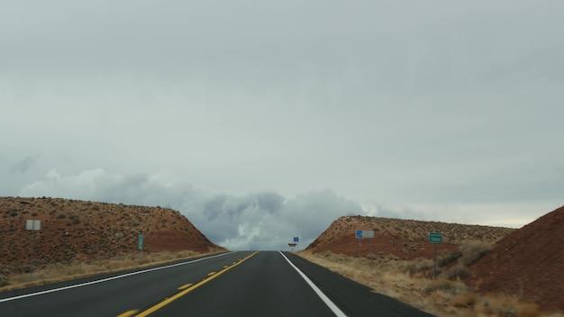 Поездка в гранд-каньон, штат аризона, сша, на автомобиле из юты. маршрут 89. автостоп по америке, местное путешествие, дикий запад, спокойная атмосфера индийских земель. вид на шоссе через лобовое стекло автомобиля.