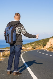 도로 여행, 여행, 몸짓, 사람 개념 - 시골에서 엄지손가락으로 차를 멈추고 히치하이킹을 하는 남자.