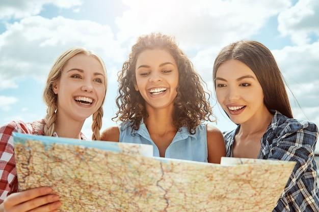 陽気で若い女性の親友グループとのロードトリップが紙を持っています