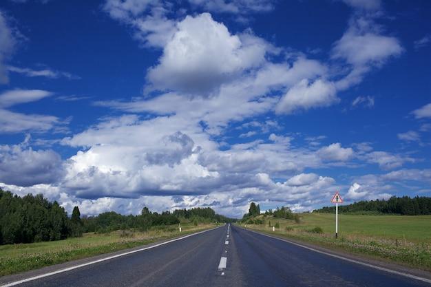 Дорога под голубым небом с облаками