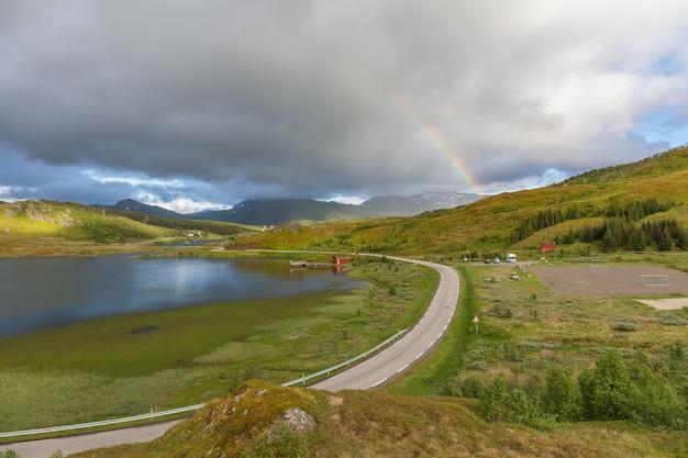 ノルウェー、ロフォーテン諸島のカラフルな虹の下の道