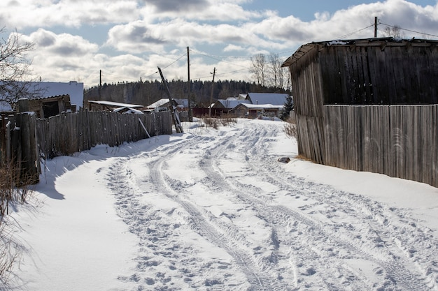 Road in the village covered with snow with traces of car tires. high quality photo