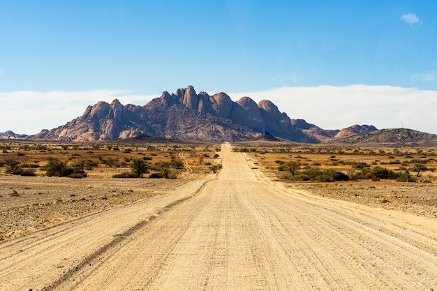 Road way to spitzkoppe mountains. the spitzkoppe, is a group of bald granite peaks located in swakopmund namib desert - namibia