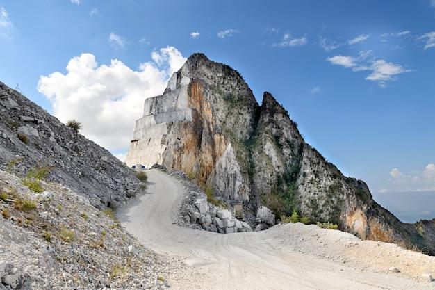 Дорога проходит мимо выкопанной горной вершины, на которой виден разрезанный камень
