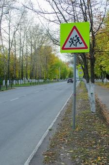 街の秋に子供たちに注意サインのある道路