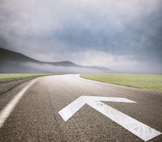 アスファルトに矢印が描かれた道路。成功の方法の概念