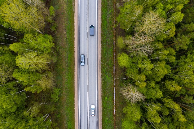 Road with cars in the forest between green trees, aerial view from drone
