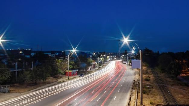 車の光跡がたくさんある道路、それに沿った鉄道道路、照明、長時間露光ショット、キシナウ、モルドバ