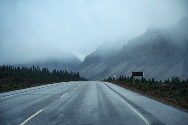 Road with rocky mountain in gloomy day at banff national park