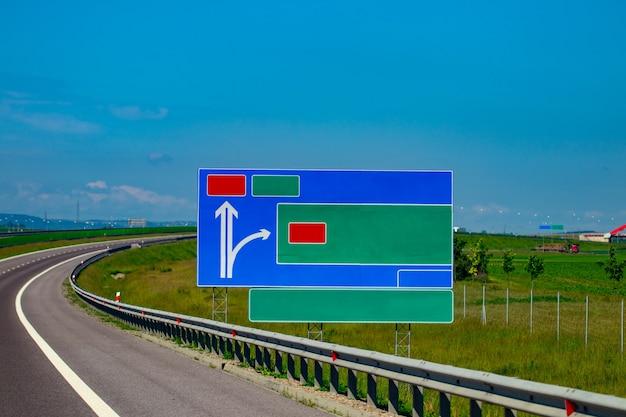 Дорога с полюсом знака и голубым небом с облаками.