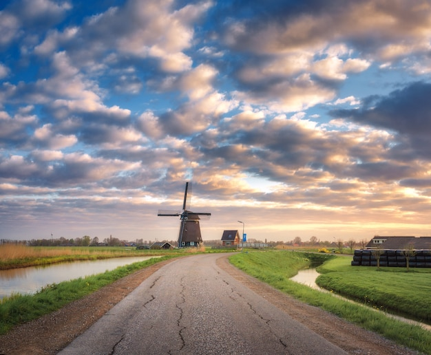 Road with windmill at sunrise in netherlands