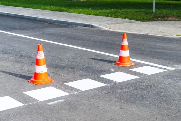 도로가 앞서 나가고, 주황색 플라스틱 콘 경고는 새로운 도로 라인에 대해 경고합니다.