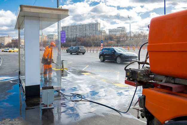 Road worker cleaning city street with high pressure power washer, moscow, russia
