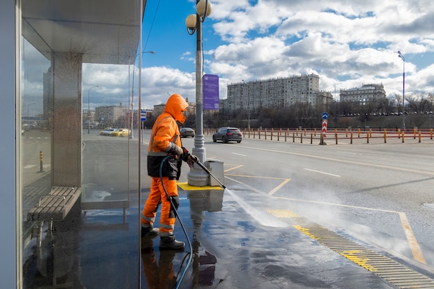 Road worker cleaning dirty public transport stops, moscow, russia
