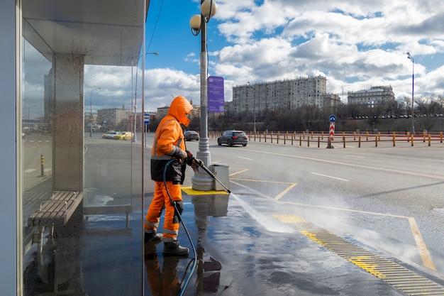 Дорожник убирает грязные остановки общественного транспорта, москва, россия
