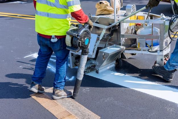 道路工事中に熱可塑性スプレーマーキングマシンで路面に白い線を塗る道路作業員