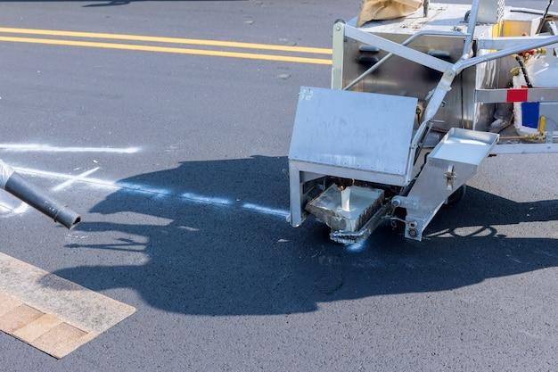 도로 작업자는 핫멜트 스크라이빙 기계를 사용하여 아스팔트 도로에서 라인을 페인팅합니다.