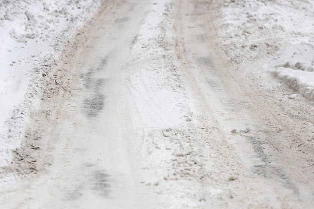The roadway is covered with snow with traces of car tires. high quality photo