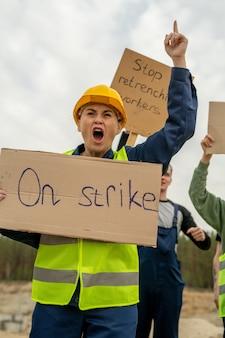 Ревущая толпа строителей с плакатами бастующих