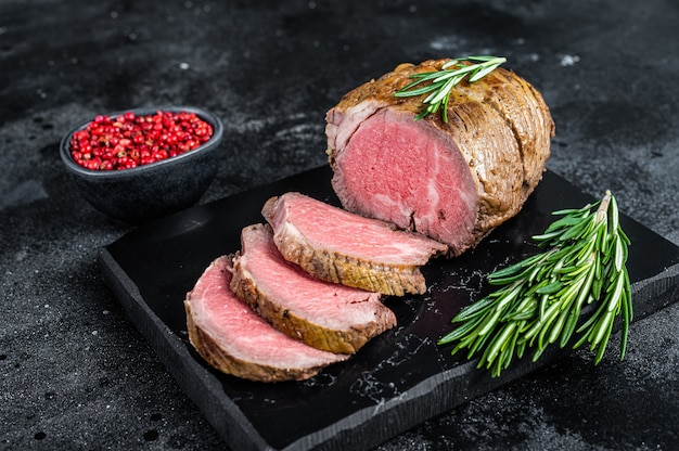 Roast beef fillet tenderloin meat on a marble board. black background. top view.
