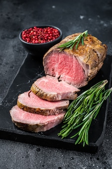 Roast beef fillet tenderloin meat on a marble board. black